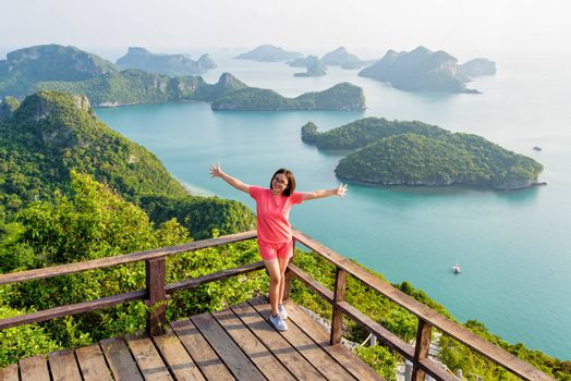 Woman tourist standing posing on the podium is peak view point of Ko Wua Ta Lap and beautiful nature landscape of island and sea in Mu Ko Ang Thong National Marine Park, Surat Thani, Thailand