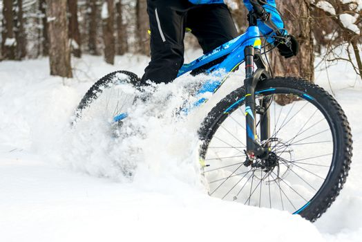 Cyclist Drifting on the Mountain Bike in the Beautiful Winter Forest. Extreme Sport and Enduro Biking Concept.