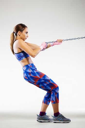 girl kickboxer pulling a chain with pink hand wraps