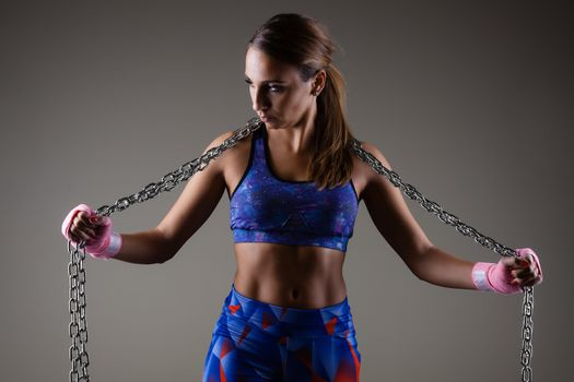 girl kickboxer holding a chain with pink hand wraps