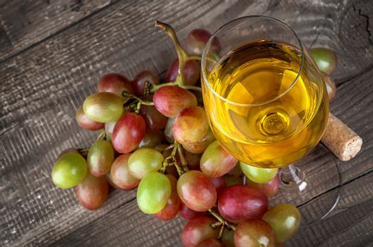 Glass of white wine with a cluster of grapes