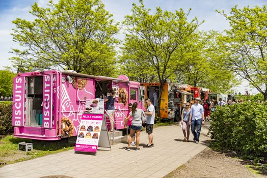 Montreal, Canada - May 28, 2017: People walking outside looking for some street food during a bright sunny day, on May 28, 2017 in Montreal Canada