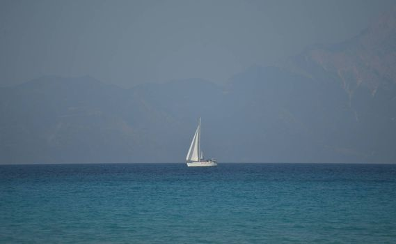 A white sailboat at sea in a hazy afternoon.