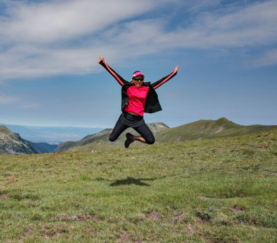 A girl is jumping high in the air with mountains as background.