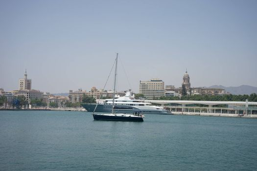A blue boat sails in the ocean in Malaga, Spain, Europe on a summer day