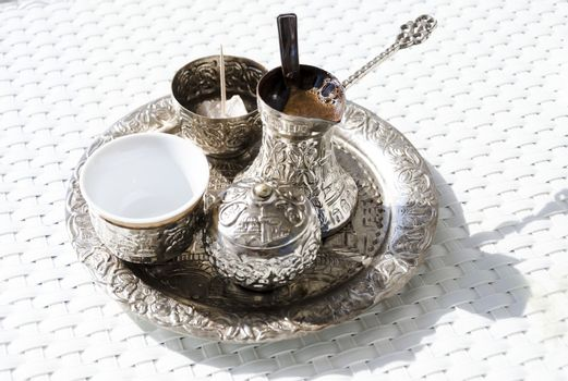 A metallic tray with copper plated cezve (džezva) filled with traditional foam Bosnian coffee, a silver pot with turkish delight, rahat lokum, a clay cup and sugar cube pot served in an ornament Sarajevo set.