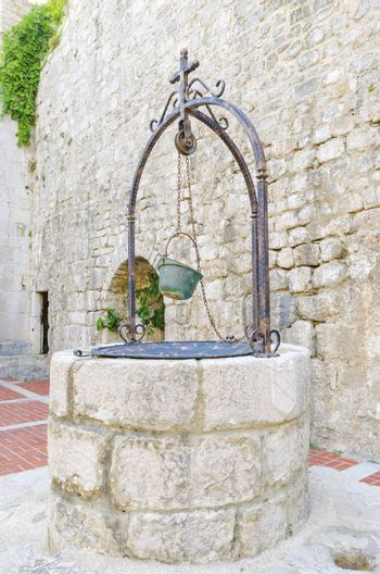 The interior of the Frankopan Castle, at Kamplin square in Krk, Croatia - Frankopanski Kastel, part of the medieval city walls. View of the well, stern with a soldier helmet as a bucket