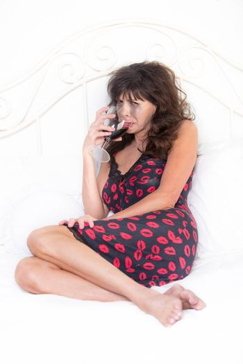 Upset mature woman crying and drinking red wine in bed