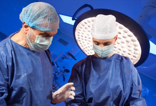 Couple of doctors are performing surgery in modern operating room.