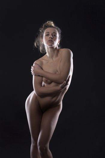 nude woman standing on black background