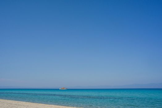 An empty beautiful seashore with clear sky and a tourist boat.