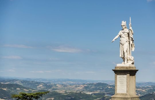 view of the ancient statue of liberty against the bright blue sky in San Marino Republic