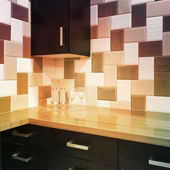 Kitchen cabinets and tiled backsplash in warm colors