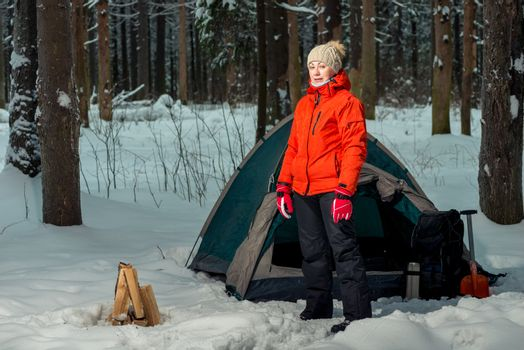 woman near a tent at a camping site in a winter forest in the mo
