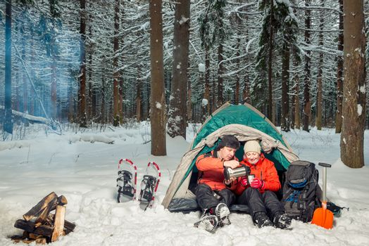 desperate tourists with tea at halt in the winter cold forest