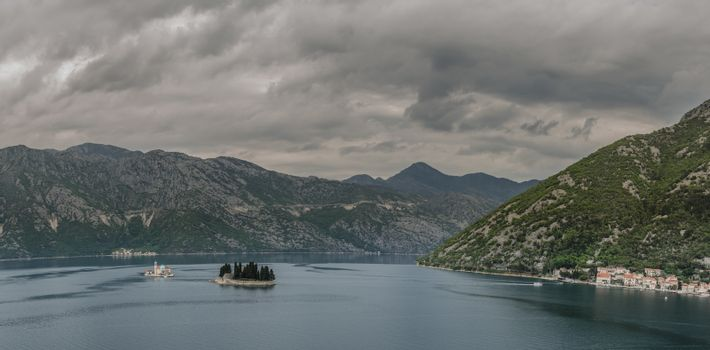 island with church and mountains in Kotor panorama view
