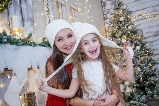Cute girl in white hat with mother under Christmas tree