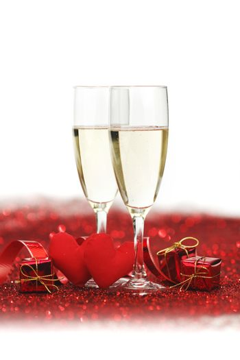 Glasses with Champagne and handmade hearts on red glitters isolated on white background