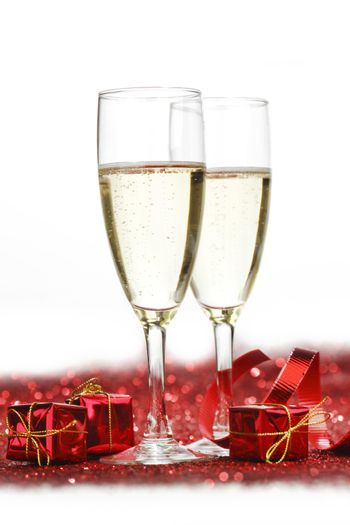 Glasses with Champagne and gifts on red glitters isolated on white background