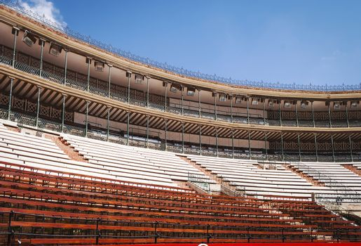 view from below of a stadium with covered tribunes and wooden seats