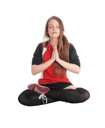 A young slim woman sitting in a joga pose with her eyes closed and meditating and her legs crossed, isolated for white background