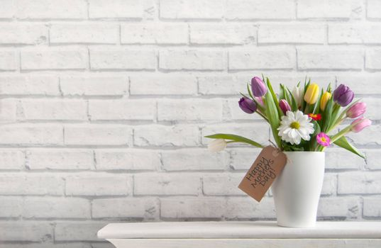 Mothers day spring flowers inside a pot on top of a fireplace mantelpiece with label