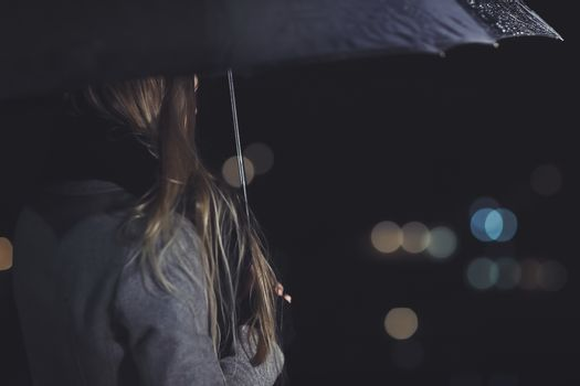 Female outdoors in rainy night, rear view of the elegant woman under black umbrella looking on the city lights, city life, loneliness and melancholy concept