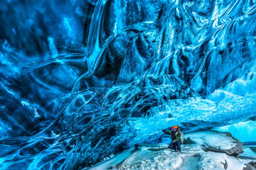 Tourist discovering the ice cave, active traveler man enjoying beauty of a glacial cave, extreme winter vacation, Skaftafell national park, Vatnajokull, Iceland