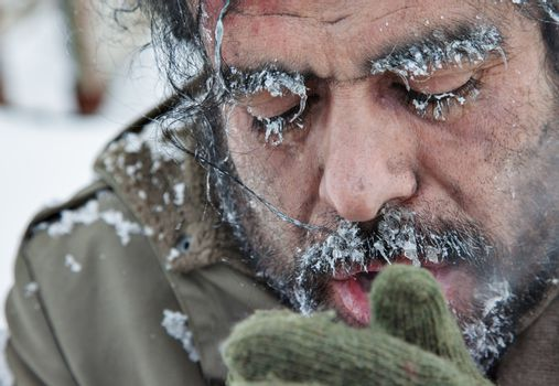 A close-up portrait of a freezing man, homeless, refugee, outdoors in a cold winter weather.