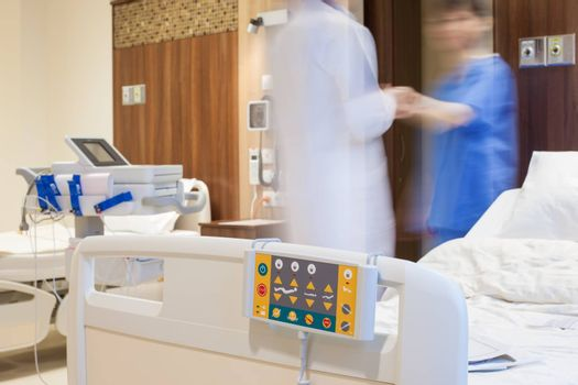 Blurred figures of doctor and a patient in modern hospital room.