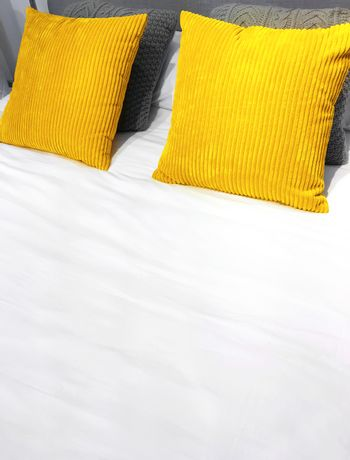Bed with bright yellow velveteen cushions