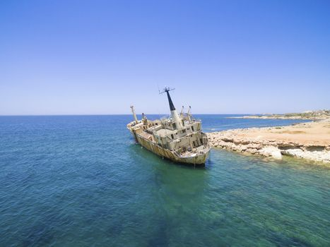 Aerial view of the abandoned ship wreck EDRO III in Pegeia, Paphos, Cyprus. The rusty shipwreck is stranded on the Peyia rocks at the kantarkastoi sea caves near Coral Bay in Pafos, standing at an angle near the shore.