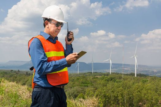Male Architect or Engineer, use Hand-Held Transceiver Radio and Digital Wireless Tablet Device, working at Wind Turbine Power Generator Field as Infrastructure Construction Project Development