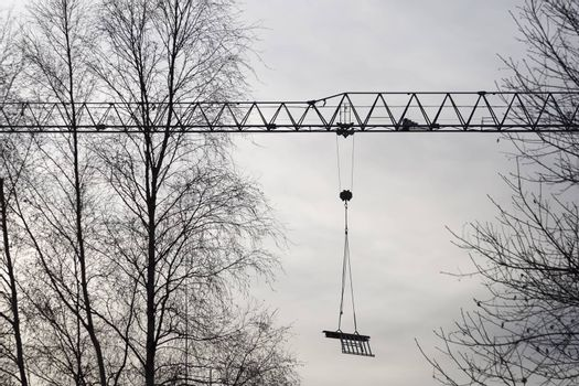 Construction Crane with Trees and a cloudy sky.