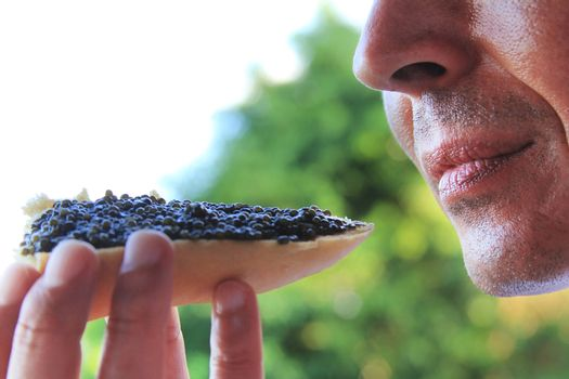 Adult man eating a sandwich with black caviar
