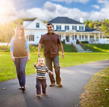 Happy Mixed Race Family Walking in Front of Beautiful Custom Home.
