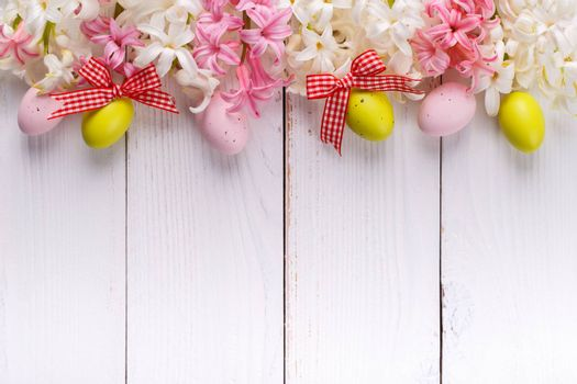 Easter background with colorful eggs ,hyacinth flowers and ribbons on white wooden board