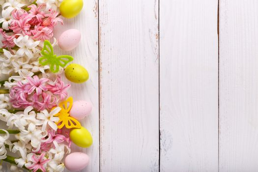 Easter background with colorful eggs ,hyacinth flowers and butterflies on white wooden background
