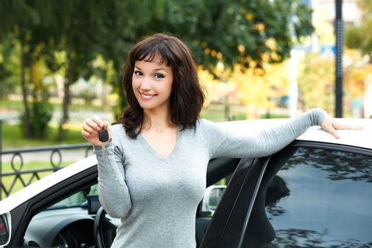 Happy owner of a new car, smiling cute young girl showing a key
