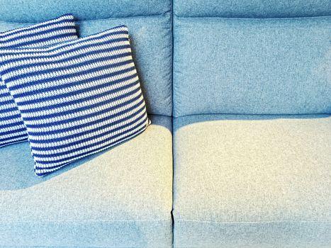 Striped cushions on a blue textile sofa