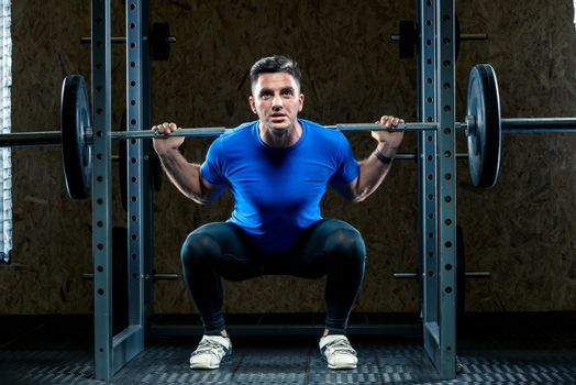 horizontal portrait of an athlete with a barbell makes an effort