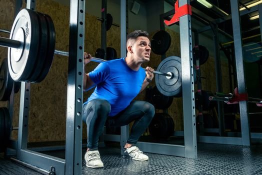 bodybuilder in a blue T-shirt raises a bar weighing 60 kg in the