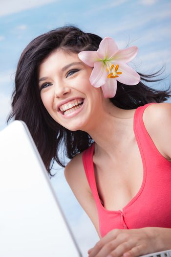 Beautiful laughing girl with lilium in her hair behind laptop