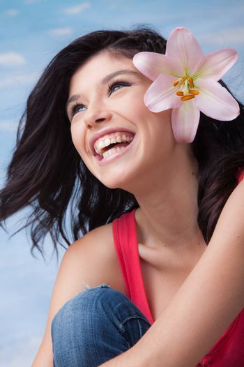 Portrait of an young beautiful laughing girl with lilies in her hair.