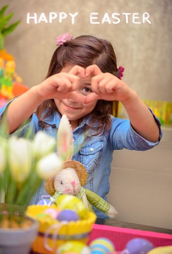 Cute little girl preparing to happy Easter holiday with her little friend bunny toy, showing heart gesture, decorating eggs in different colors, love and observance of traditions concept