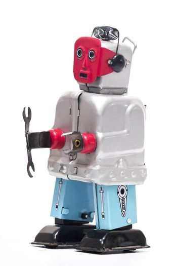 Vintage retro red face tin toy robot isolated on a white background.
