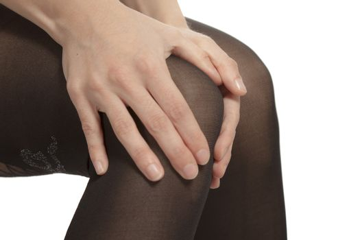 Close-up of female legs with pantyhose. Woman is rubbing her knee to relax pain.