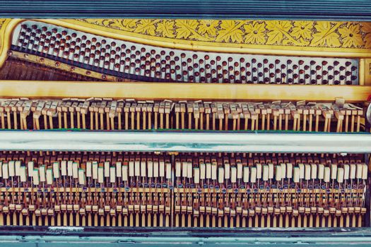 Old piano inside mechanics, colorful hammers and strings background