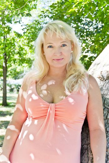 Portrait of blond woman with sapphirine eyes in summer time