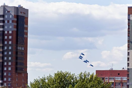 Six military airplanes are flying under city in blue sky